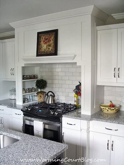 Custom kitchen range hood with spice shelves built into the sides