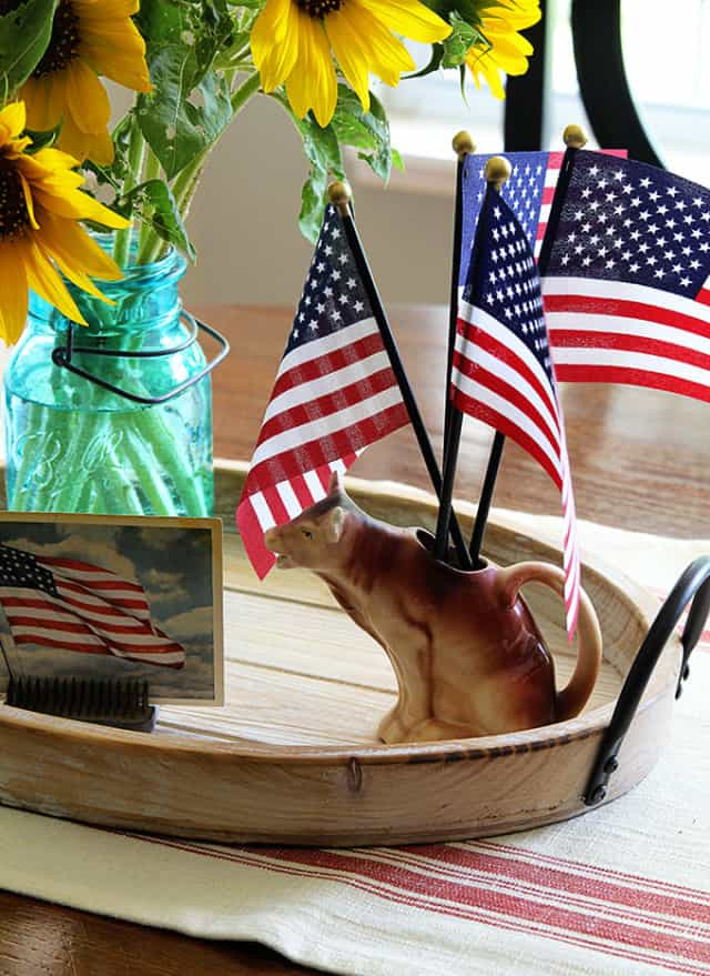 round wood tray with American flags in a pitcher