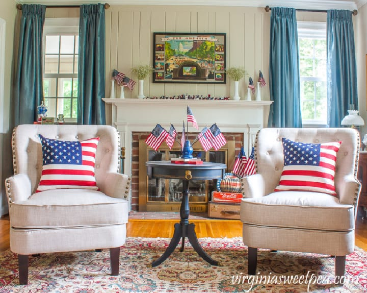 two white chairs in front on a white fireplace with patriotic decor