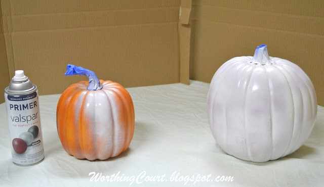 Spray painting pumpkins before decoupaging with decorative napkins