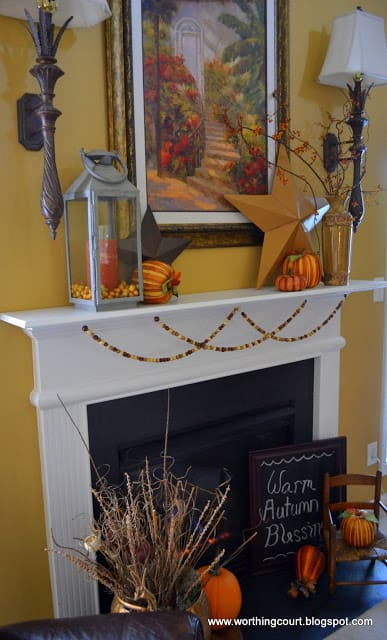 Faux pumpkins, a lantern, metal stars and wooden beads make up the Fall decor on this mantle