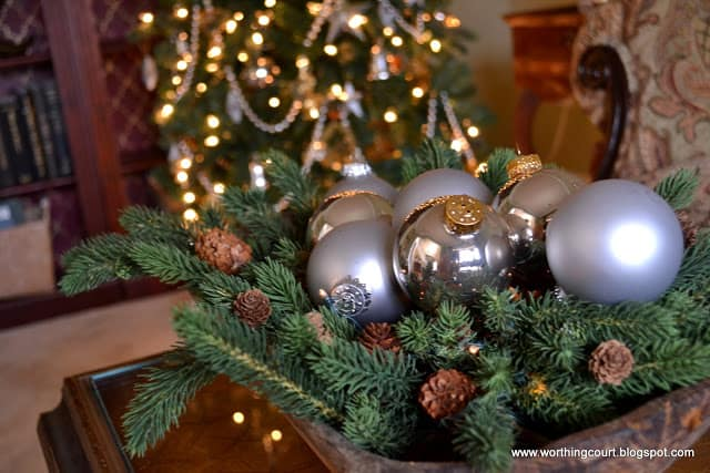 Christmas arrangement in a dough bowl using greenery and silver ornaments via Worthing Court blog