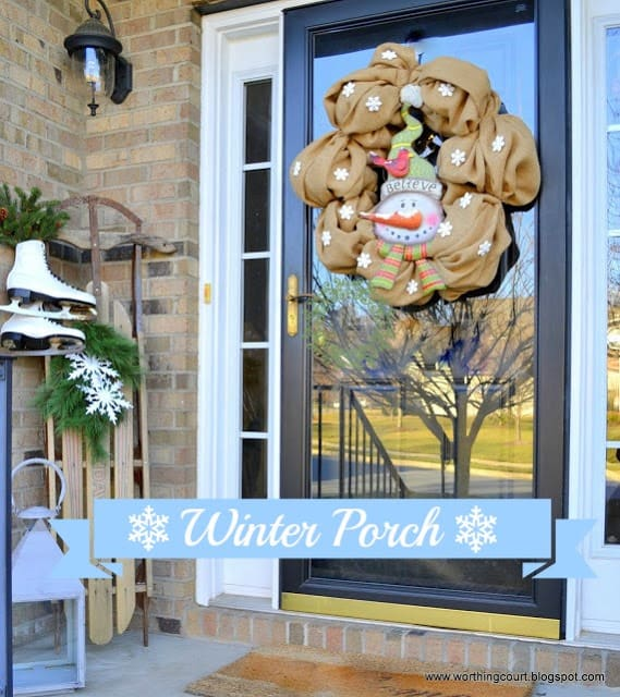 Winter front porch with a snowman wreath, vintage sled and vintage ice skates via Worthing Court blog