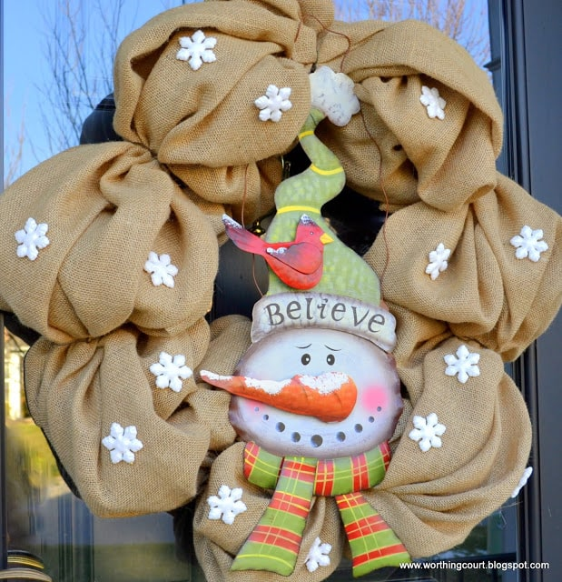 A burlap wreath with a tin snowman looks great on a winter front porch.