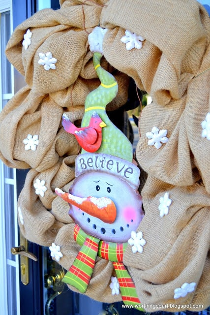 A burlap wreath with a tin snowman on a winter front porch