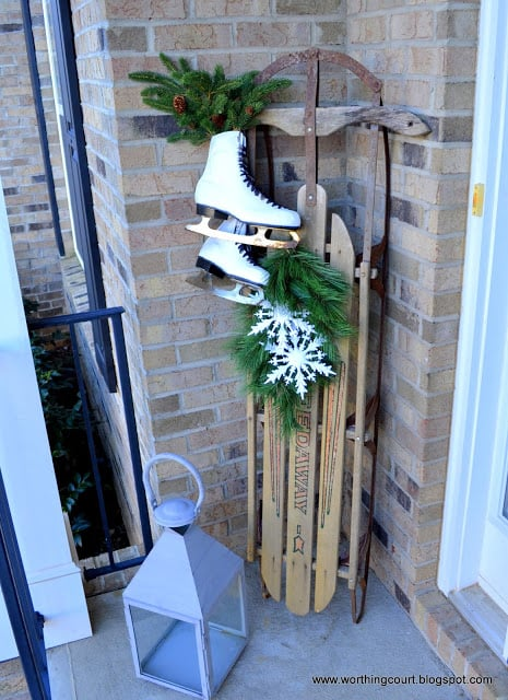 Worthing Court: Winter front porch with a vintage sled, ice skates, greenery and burlap snowman wreath