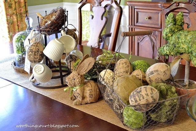 A wire basket filled with burlap eggs and orbs covered with natural elements add a lot of texture to this Easter centerpiece.