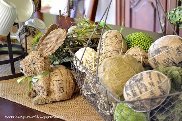 An Easter centerpiece with an aged wire basket filled with burlap eggs and a variety of decorative orbs flanked by a burlap bunny.