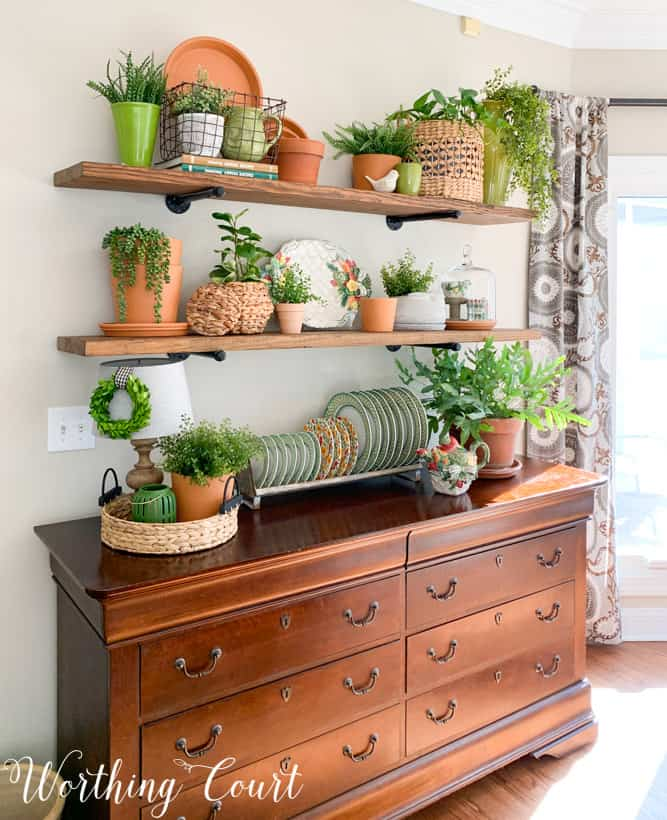 open shelves decorated for spring with terra cotta pots and greenery