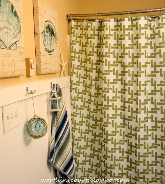 There is a green and white shower curtain hanging in the bathroom.