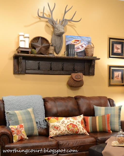 The top of a vintage mantle turned into a shelf, with added hooks and a faux deer head.