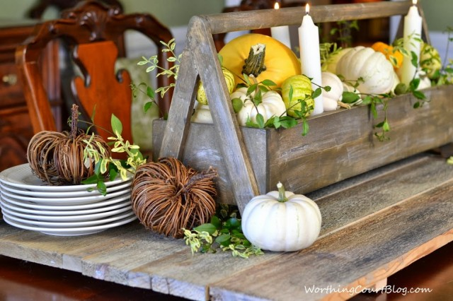Worthing Court: Wooden tool box filled with yellow and white pumpkins and fresh greenery. The aged wood makes a great base for the centerpiece.