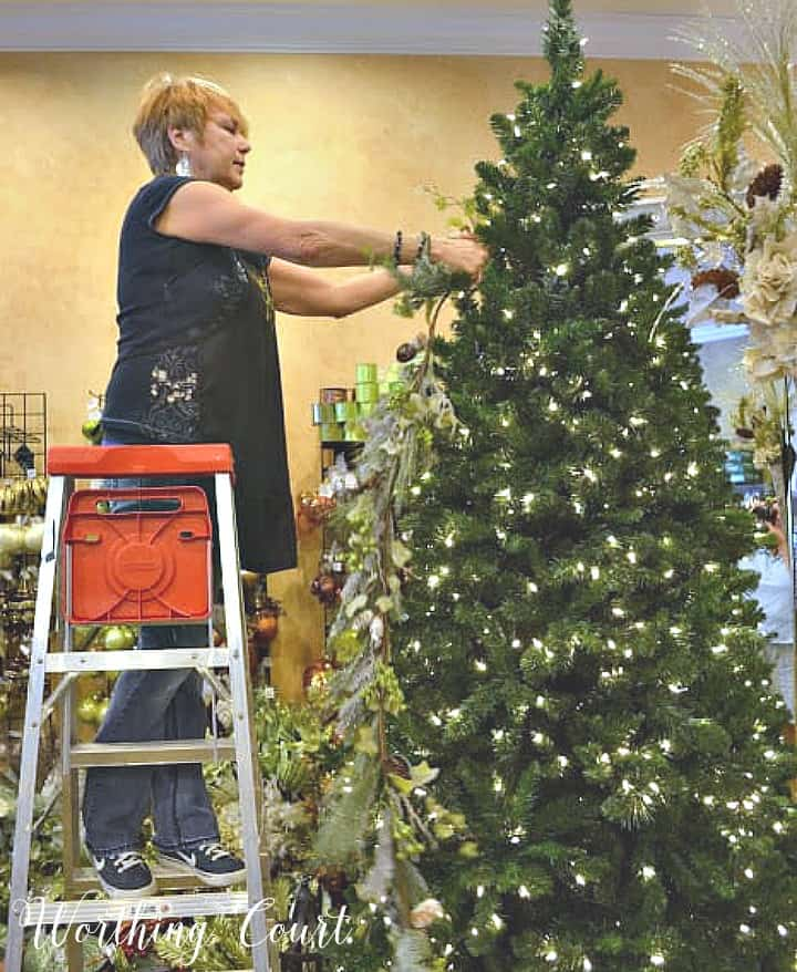 designer adding garland to a Christmas tree