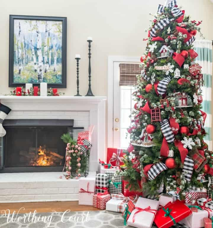 Christmas tree decorating with red ornaments and black and white ribbon