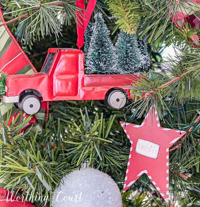 A red toy truck is wired to the Christmas tree.