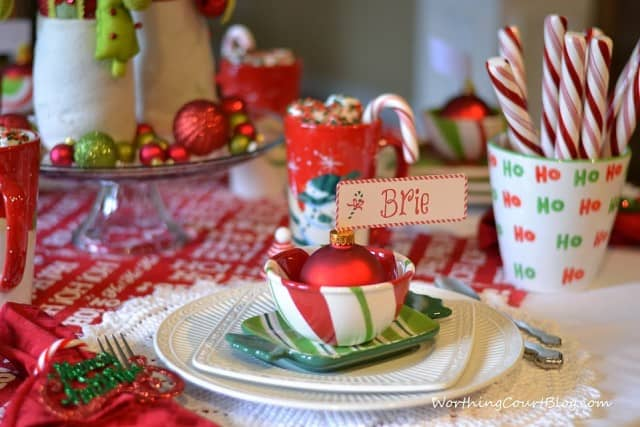 There are candy canes in a cup on the table.