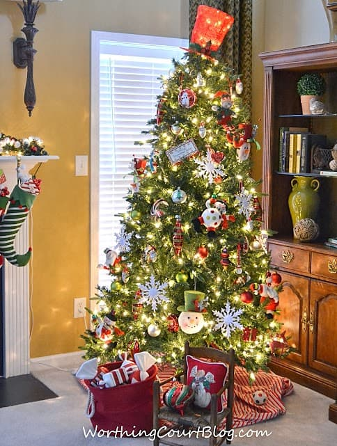 A large Christmas tree in the corner of the living room.