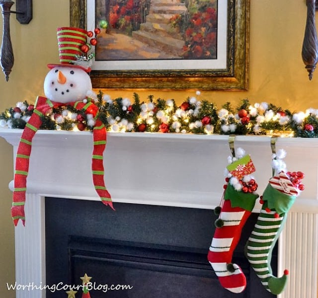 There is a cute snowman on the mantel.