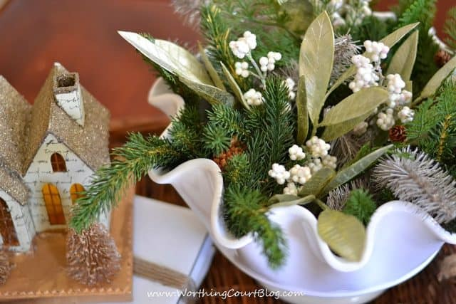 Faux greenery, leaves and berries in a fluted bowl.