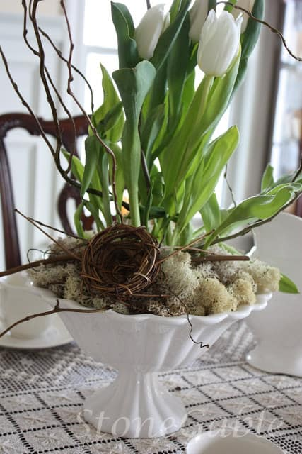 A white fluted bowl filled with spring flowers, twigs, a bird nest and bits of reindeer moss makes a lovely neutral centerpiece.
