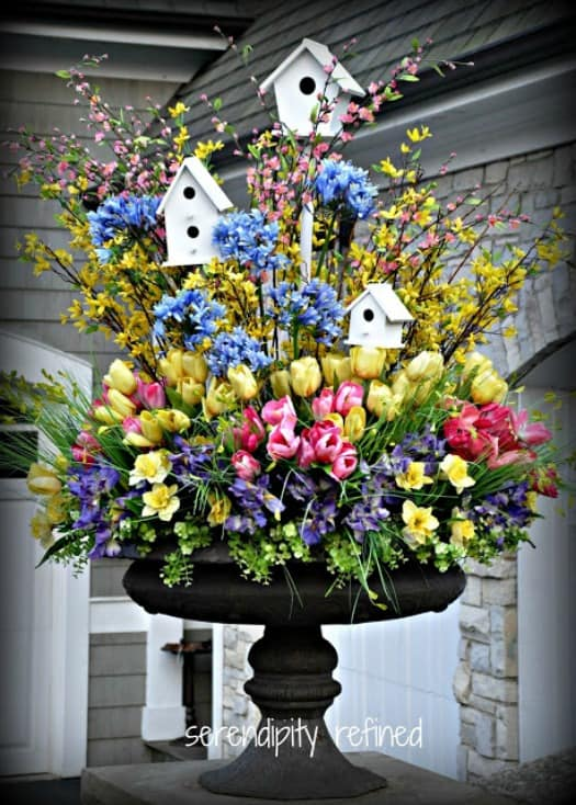 A stunning urn filled with a variety of spring flowers, greenery and birdhouses.