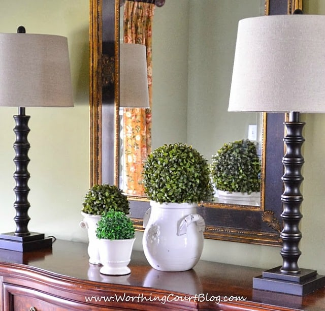 An easy spring dining room vignette made up of various sized urns topped with faux greenery orbs