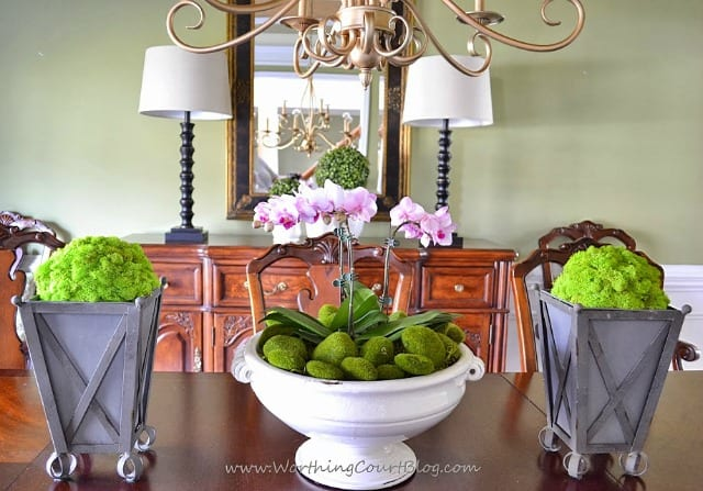 Styrofoam balls covered with reindeer moss and placed in zinc planters flank an orchid filled urn as part of spring decor in a dining room