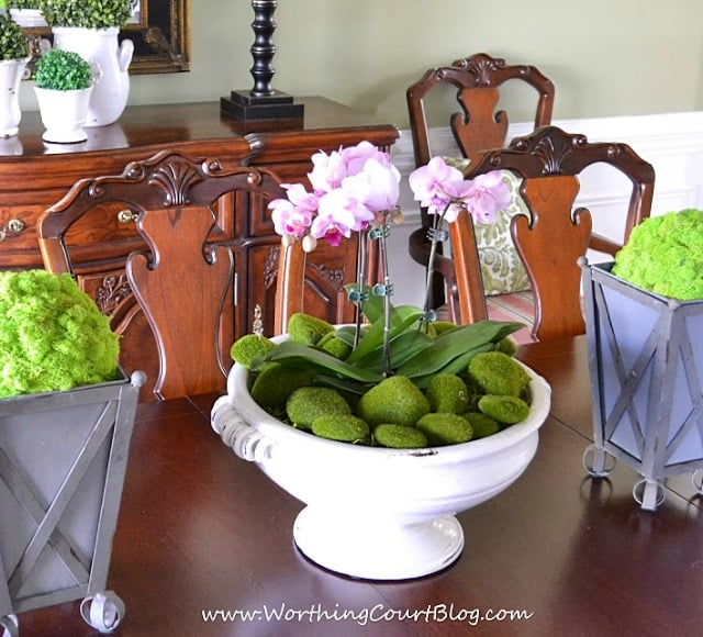 Grocery store orchids fill a large urn on a dining room table decorated for spring