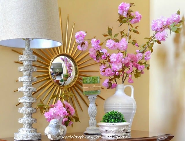 Decorate for spring for free!  Shop your yard or the woods to see all that nature has to offer this time of year.  I paired clippings from my kwanzan cherry tree with a faux boxwood orb and bright white accessories for a fresh look on my traditional foyer chest. || Worthing Court Blog