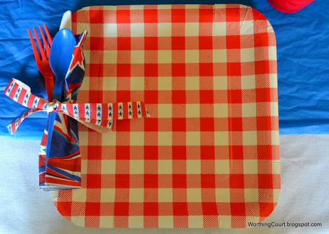 Super easy patriotic place setting using paper plates, paper napkins and plastic utensils, all from the dollar store. Use a hole punch to punch a hole into the side of the plate. Run a ribbon through the hole and tie it around a rolled up paper napkins and plastic utensils.