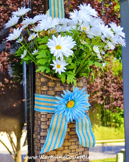 A door basket filled with daisies for summer. A door basket is so versatile. It's easy to simply change what is displayed during the different seasons and for the different holidays.
