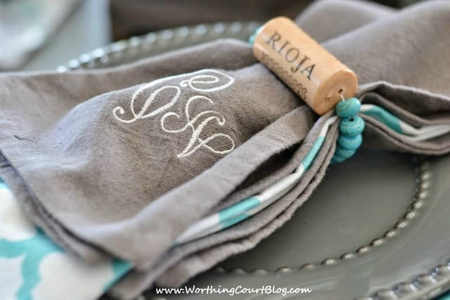 Grey napkins with a turquoise beaded string and wine cork.