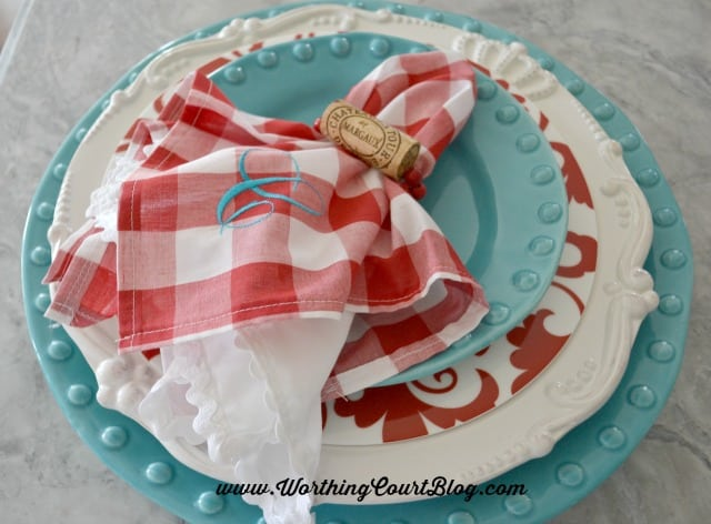 The cork napkin holder with a red and white napkin.