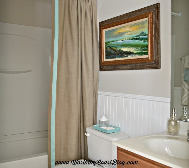 Use a drapery panel for a shower curtain. Hang a clear plastic shower curtain on a separate rod on the backside to protect it while showering. Use iron on tape to add a border of ribbon to the edge of the panel. :: worthingcourtblog.com