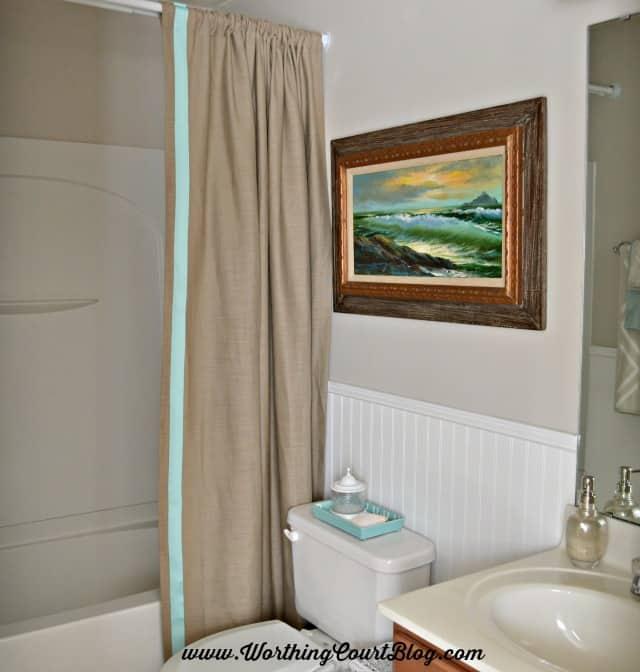 A neutral and aqua small bathroom with a beachy vibe