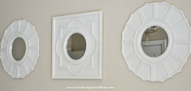 Mirrors made by spray painted ceiling medallions and hot-gluing a craft mirror to the center.