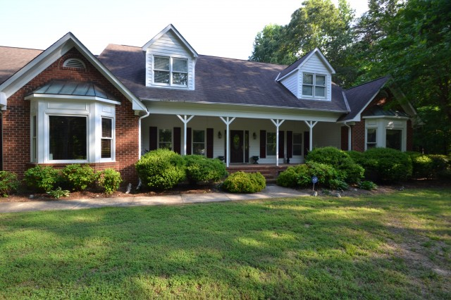 Brick ranch with twin dormers and a deep front porch