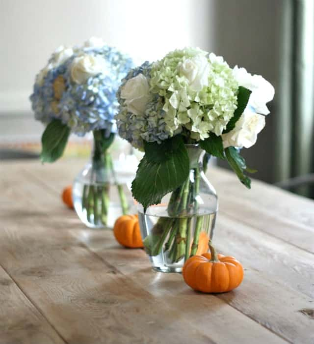 Ease into fall decorating by mixing mini pumpkins with summer flowers that are still blooming.