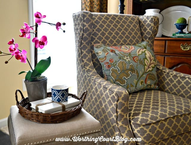 Decorative objects gathered in a round wicker tray || WorthingCourtBlog.com