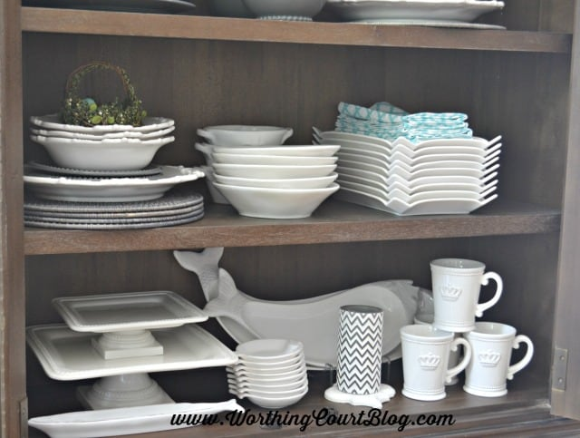 Gray and white stacked dishes and accessories in a kitchen display cabinet