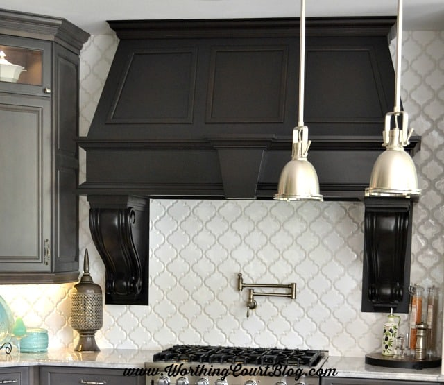 The large, white arabesque shaped tile makes the perfect backdrop for a gorgeous range hood.