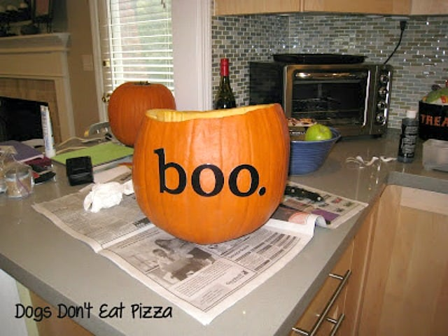 The words BOO on the pumpkin in black, stuck on with adhesive.