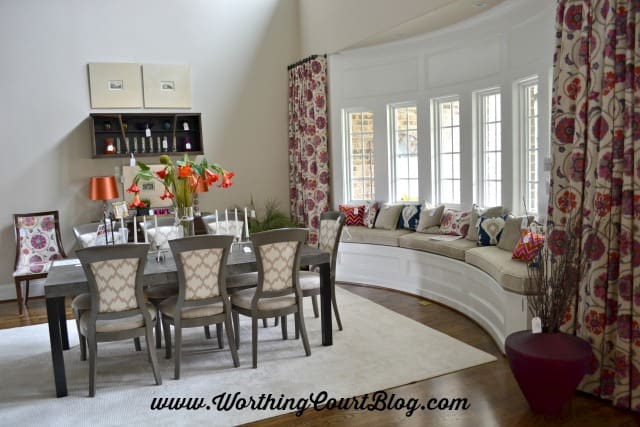 Curved window with a bench filled with multiple pillows that pull together all of the colors used in the house