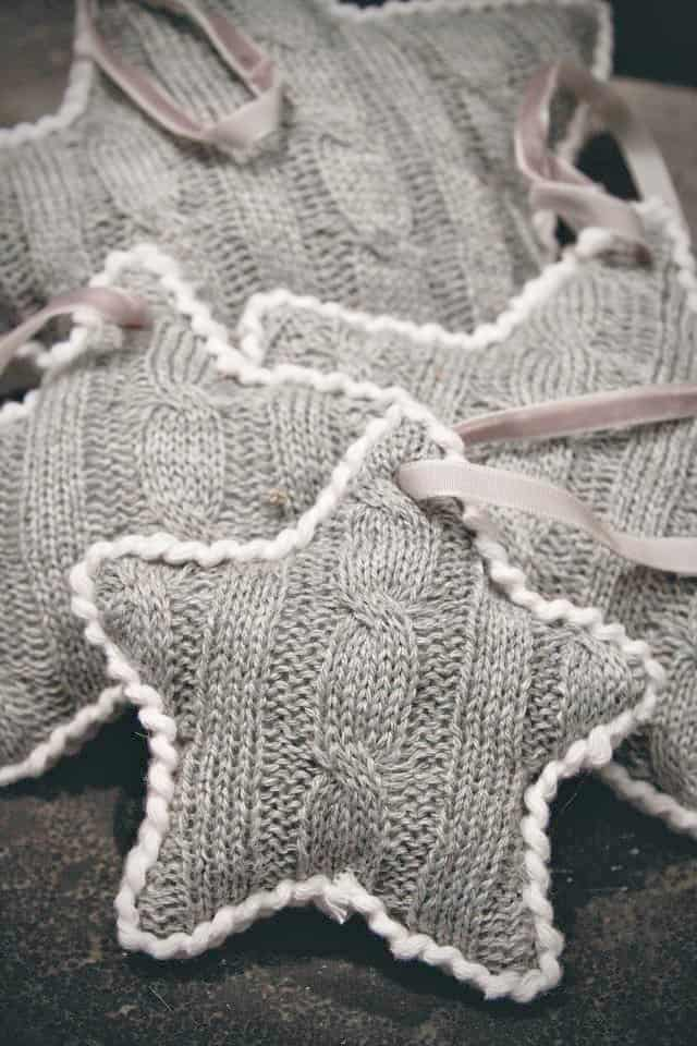 Cut out star shapes from a sweater, whip stitch the edges, leaving an opening for stuffing.  Whip stitch the opening closed once finished stuffing.  Insert a pretty piece of narrow ribbon for hanging.