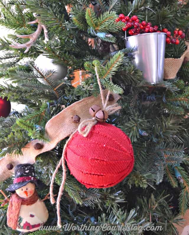 Rustic Christmas ornaments on the tree like a cute snowman and a galvanized pail filled with red berries.
