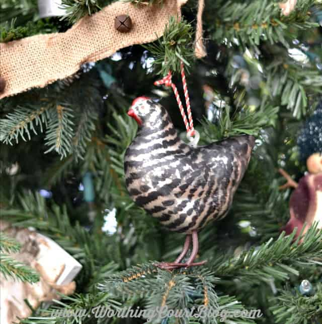 Farmhouse hen Christmas ornament hanging on the Christmas tree.
