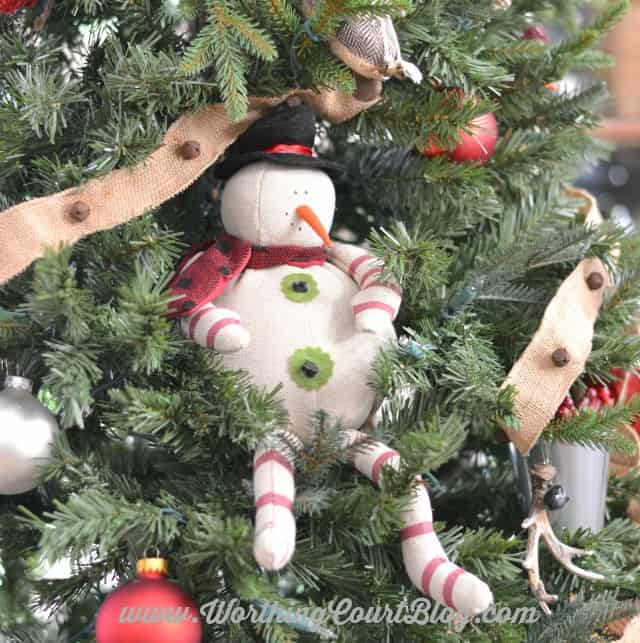 A snowman that is sitting in the Christmas treee.