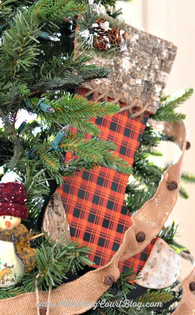 A second plaid wooden stocking on the Christmas tree.