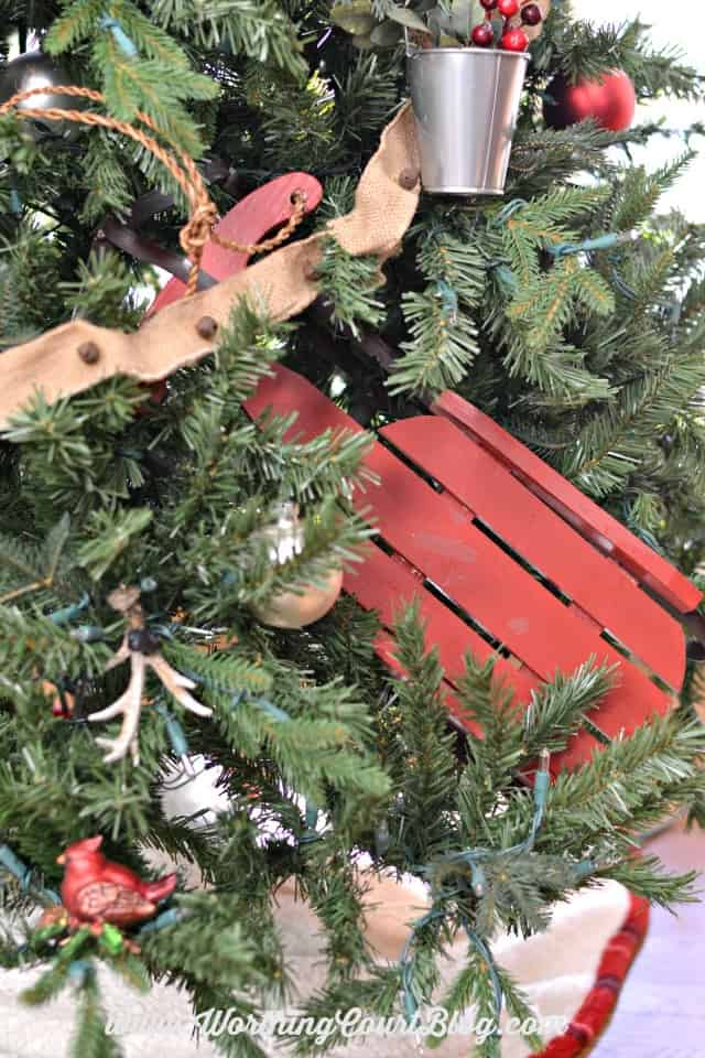 A red wooden sleigh towards the bottom of the Christmas tree.