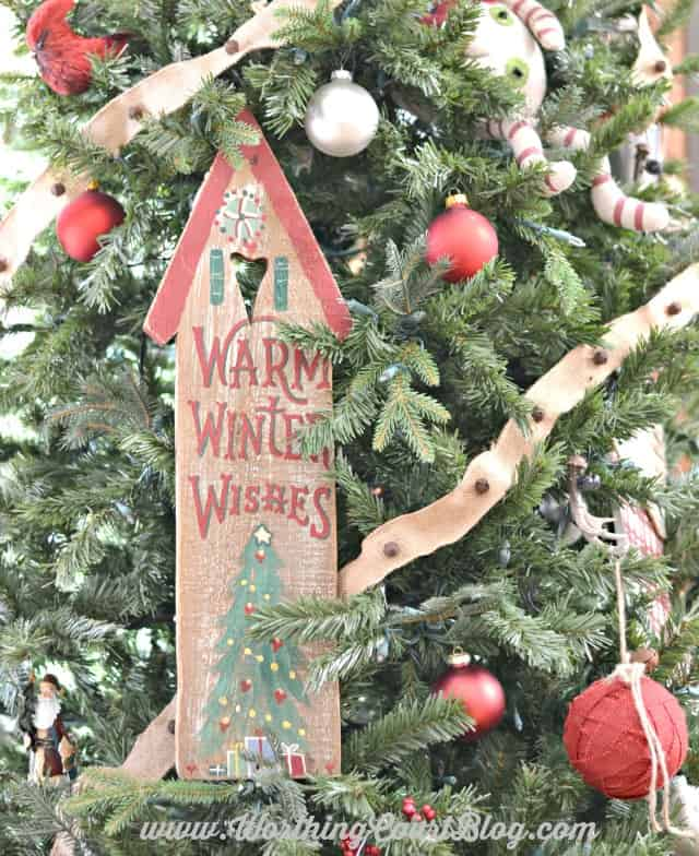 A wooden door plaque wired to a Christmas tree with green floral wire.